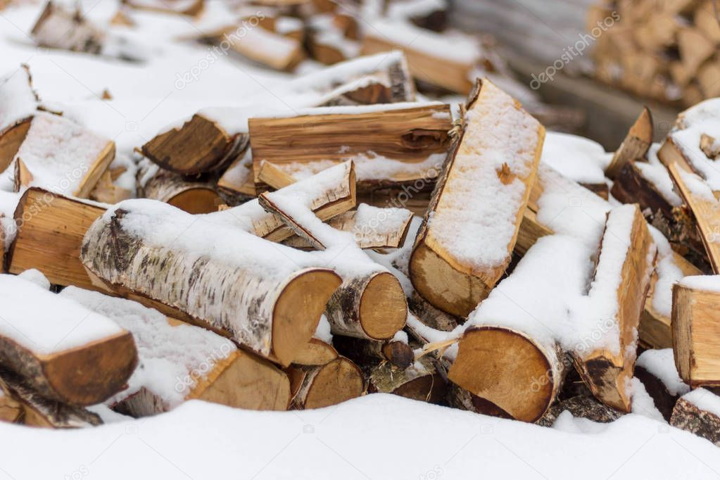 birch firewood chopped and lie under the snow
