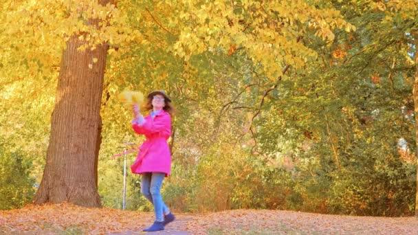 Šťastná žena hraje s podzimními listy v parku