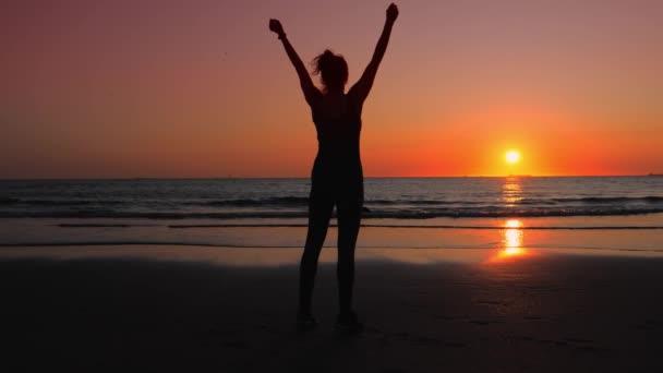 Žena ve fitness oblečení na břehu oceánu, ona má své sportovní úspěchy.