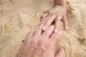 Fotografie Holding hands on a sandy beach