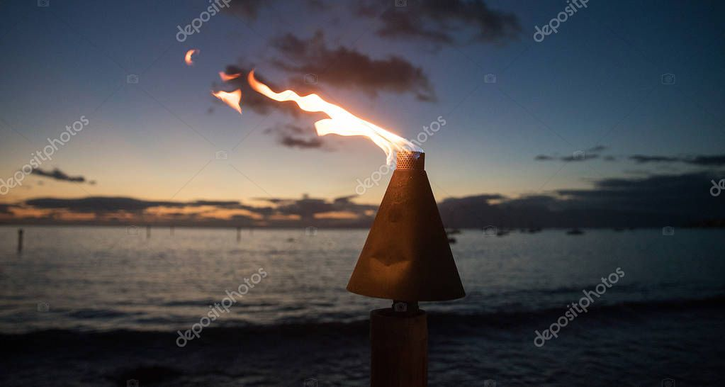 Tiki torch burning flame during evening at beach
