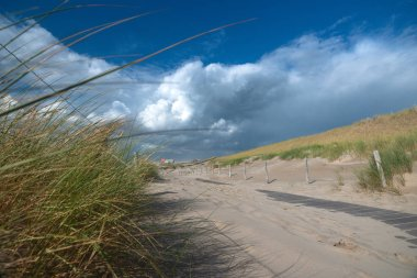 Beautiful picture with a view over the Dutch coast strip with sand dunes, wide beaches and a sunny, windy storm day