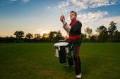 Bicí hráč nebo bubeník během venkovní focení s lampami studio v atraktivní interaktivní večer scéně