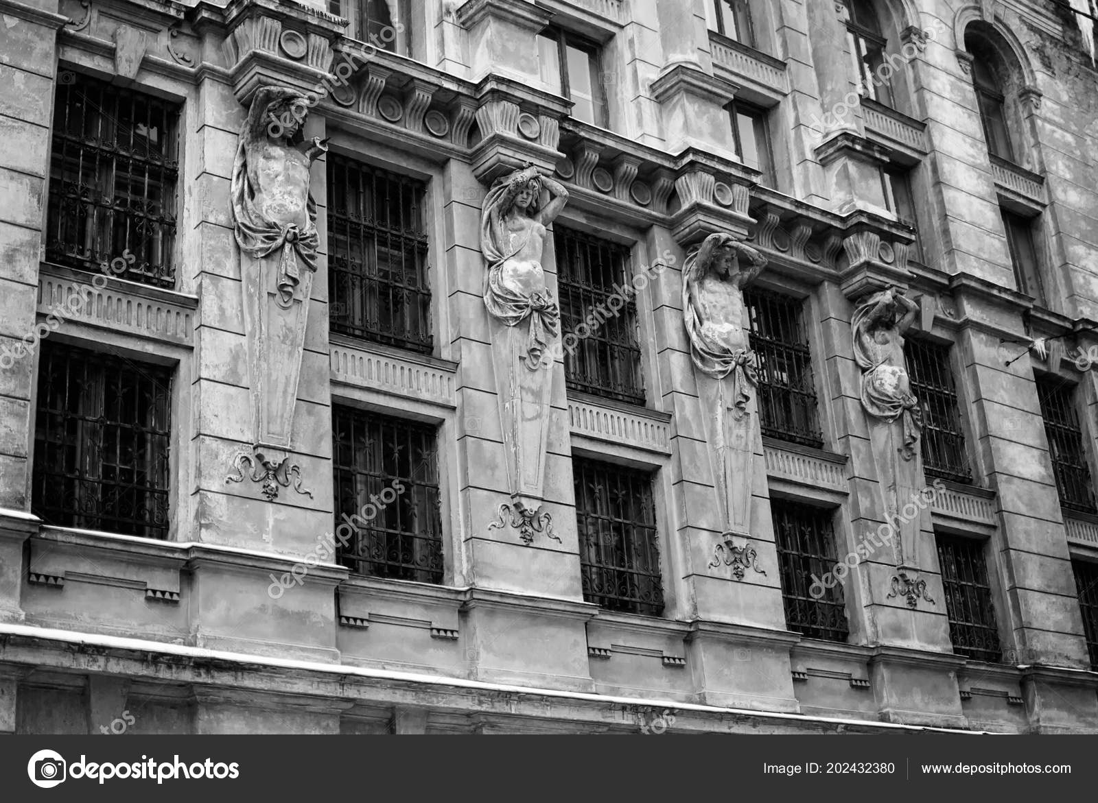 Gloomy dark house with black windows oldfashioned abandoned building ancient sculptures holding architectural elements iron bars black and white photo