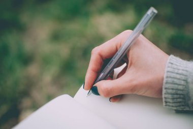 Tender girl's pale hand holding a pen and writing on the blank pages of a notebook. Concept (idea) of dreaming, planning, motivation, studying.