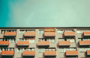 Old soviet residential building and summer blue sky. Vintage retro colors