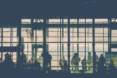 Black sillhouettes of people waiting for their train on a subway station behind glass windows filled with sunshine