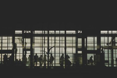 Black sillhouettes of people huttying up to take a train on a subway station behind glass windows filled with sunshine. Berlin, Germany