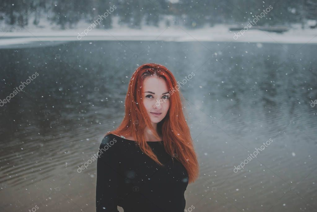 Joyful handsome black-eyed redhead girl looking at the camera. Splendid shady black mountain lake reflecting trees of forest behind her back.