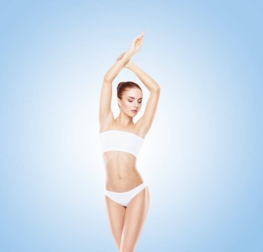 Sporty girl posing in swimsuit on blue background. Sport, fitness, nutrition and beautiful body shape concept.