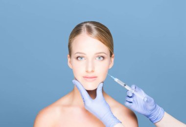 Young and beautiful woman having skin injections over cyan background. Plastic surgery concept.