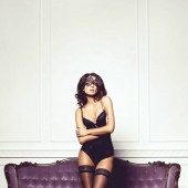 Sexy and beautiful woman in erotic lingerie and stockings posing on a violet sofa in vintage interior.