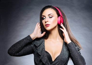 Portrait of young, beautiful and sexy dj girl listening to the music in a headphones
