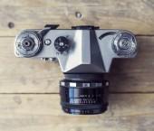 Fotografie Retro slr fotoaparát přes dřevěné pozadí. Ročník fotografické kamery