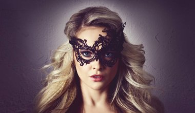 Portrait of young woman in vintage mask. Face of attractive blond girl with beautiful hairstyle.