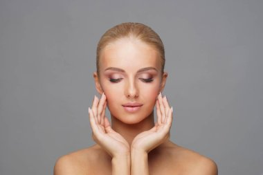 Beautiful face of young and healthy girl over grey background. Skin care, cosmetics and face lifting concept.