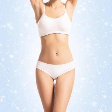 Close-up body of a young, fit and sporty female body in white underwear. Skincare, fitness, dieting, fat loss and sport concept. Winter background.