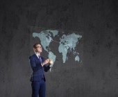 Üzletember állandó smartphone. Világ megjelenítése háttér. Üzleti, a globalizáció, a koncepció. Kollázs