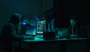Wanted hackers coding virus ransomware using laptops and computers in the basement. Cyber attack, system breaking and malware concept.