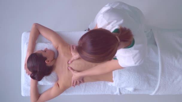 Junge Frau im Spa. Traditionelle heilende Therapie und Massage Behandlungen. Gesundheit, Haut Pflege, Massage, Osteopathie und Erholung-Konzept.
