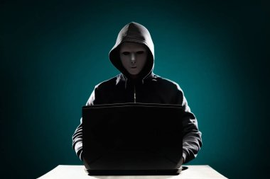 Portrait of computer hacker in white mask and hoodie. Obscured dark face. Data thief, internet fraud, darknet and cyber security concept.