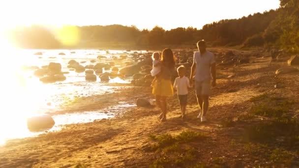 Šťastná rodina prochází kolem moře. Pláž a oceán. Teplé barvy při západu slunce nebo východu slunce. Milující rodiče a krásné děti. Koncepce lásky a rodičovství.