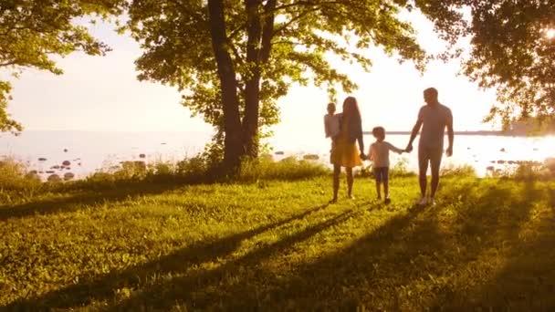 glückliche Familie zu Fuß in der Nähe des Meeres. Feld und Bäume in der Landschaft. warme Farben des Sonnenuntergangs oder Sonnenaufgangs. liebevolle Eltern und schöne Kinder. Liebe und Elternschaft.