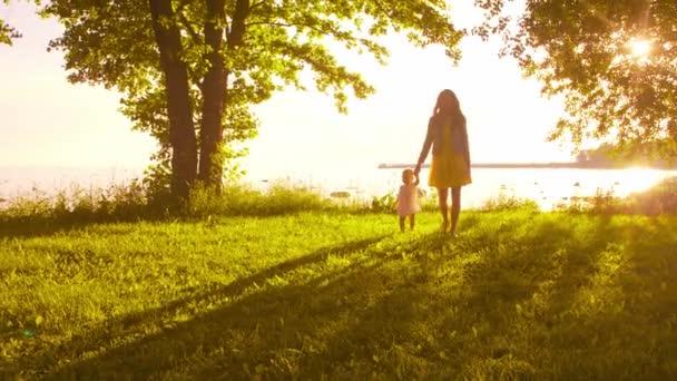 glückliche Familie zu Fuß in der Nähe des Meeres. Feld und Bäume in der Landschaft. warme Farben des Sonnenuntergangs oder Sonnenaufgangs. liebevolle Mutter und schöne Tochter. Liebe und Elternschaft.