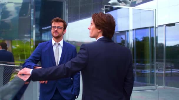 Magabiztos üzleti emberek beszélnek a modern irodaépület előtt. Üzletember és kollégája. Banki és pénzügyi piaci koncepció.