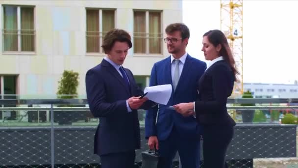 Confident businesspersons talking in front of modern office building. Businessmen and businesswoman have business conversation. Banking, professional job and financial market concept.