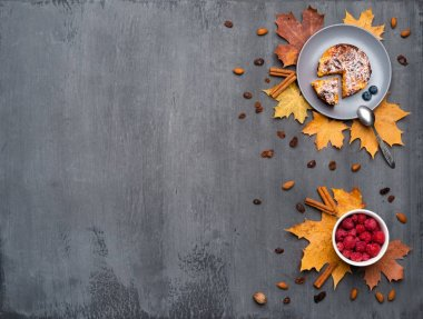 Seasonal autumn background. Frame of colorful maple leaves and a nutmeg, cake, raspberries and cinnamon over grey texture.