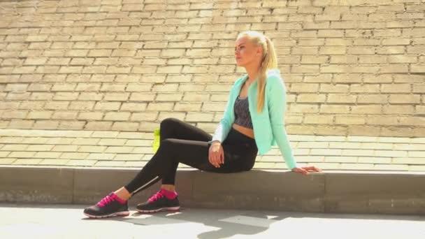Mladá, přitažlivá a sportovně plavovlasá dívka ve sportovním oblečení relaxace venku. Koncepce zdravotní péče, sportu, vhodnosti a životního stylu.