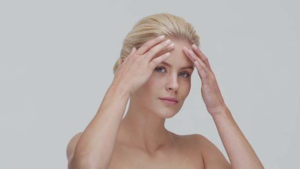 Studio portrét mladé, krásné a přírodní blond ženy, aplikující krém na péči o pleť. Zdvihání obličeje, kosmetika a make-up.