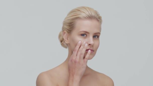 Stúdió portré fiatal, gyönyörű és természetes szőke nő alkalmazó bőrápoló krém. Arcfelvarrás, kozmetikumok és smink.