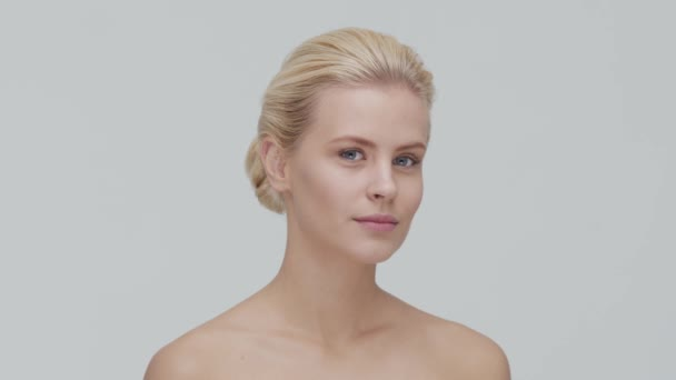 Studio portrait of young, beautiful and natural blond woman applying skin care cream. Face lifting, cosmetics and make-up.
