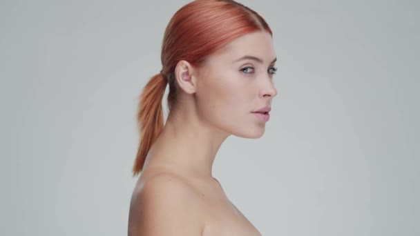 Studio portrait of young, beautiful and natural redhead woman applying skin care cream. Face lifting, cosmetics and make-up.
