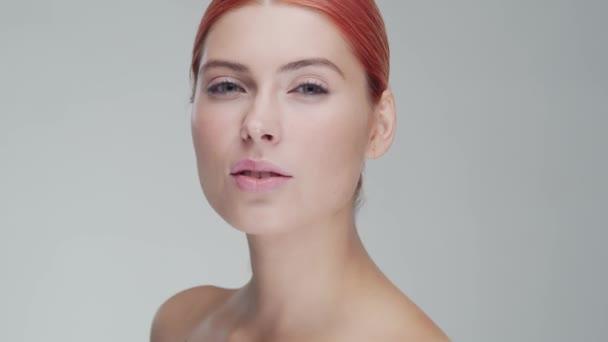 Stúdió portré fiatal, gyönyörű és természetes vörös hajú nő alkalmazó bőrápoló krém. Arcfelvarrás, kozmetikumok és smink.