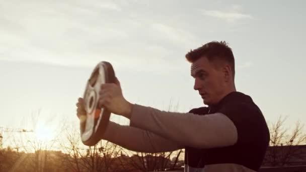 Mladý a fit muž má večerní cvičení venku. Pozadí západu slunce. Fitness a sportovní koncepce.