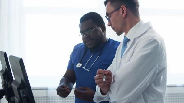 Arzt und Chirurg arbeiten im Krankenhausbüro mit Computertechnologie. Mediziner in der Klinik. Tageslicht. Gesundheitswesen, Medizin, Teamwork-Konzepte.