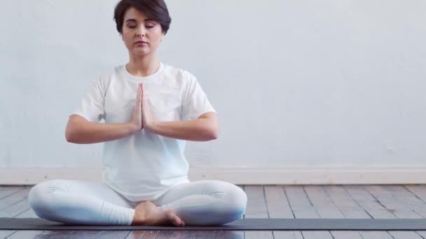 Fiatal és fitt nő jógázik az osztályban. Nyújtás gyakorlat a nappali fényben. Sport-, fitnesz-, egészség- és életmódkoncepciók.