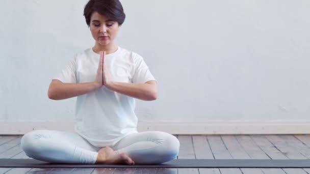 Junge und fitte Frau beim Yoga in der Klasse. Dehnübungen im Tageslicht. Sport, Fitness, Gesundheitswesen und Lifestylekonzepte.