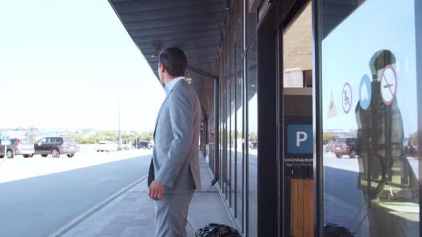Elegáns üzletember sétált bőrönddel a reptéren. Fiatal postai vállalkozó a formalwear-ben. Üzleti út és utazási koncepciók.