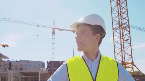Professional builder standing in front of construction site. Foreman in hardhat helmet and vest. Office building and crane background. Business, real estate and investment concepts.
