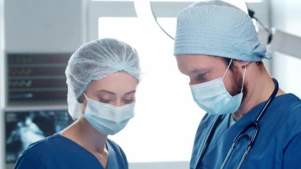Fachärzte für Notfallmedizin. Porträt des Chirurgen und der Krankenschwester in Schutzmasken, die chirurgische Operationen durchführen.