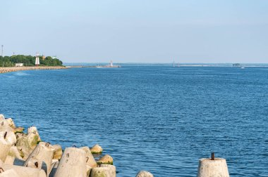 Jetty with towers and buoys. Beautiful seascape, copy space. Breakwater for protect ships at shipyard from waves