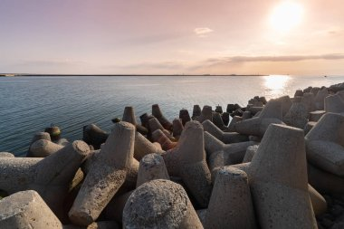 Tetrapod breakwaters in sea water. Beautiful sunset seascape with concrete tetrapodes for protect coastal structures from storm sea waves, effects of weather and longshore drift