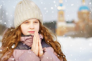 Little girl prays in front of the church. Baptism, christmas concept.