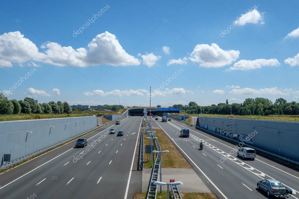 SCHIEDAM, NETHERLANDS - JUL 31, 2018 : Modern deepened Highway A4, leading into a tunnel under the urban area close to Rotterdam Netherlands. The deepened motorway is built to save the nature reserve.