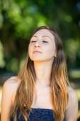 Portréja fiatal tinédzser zárt szemmel a szabadban egy parkban.