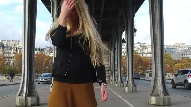 Mladá krásná blondýna žena portrét poslech hudby se sluchátky při chůzi pod Bir Hakeim most v Paříži, Francie.